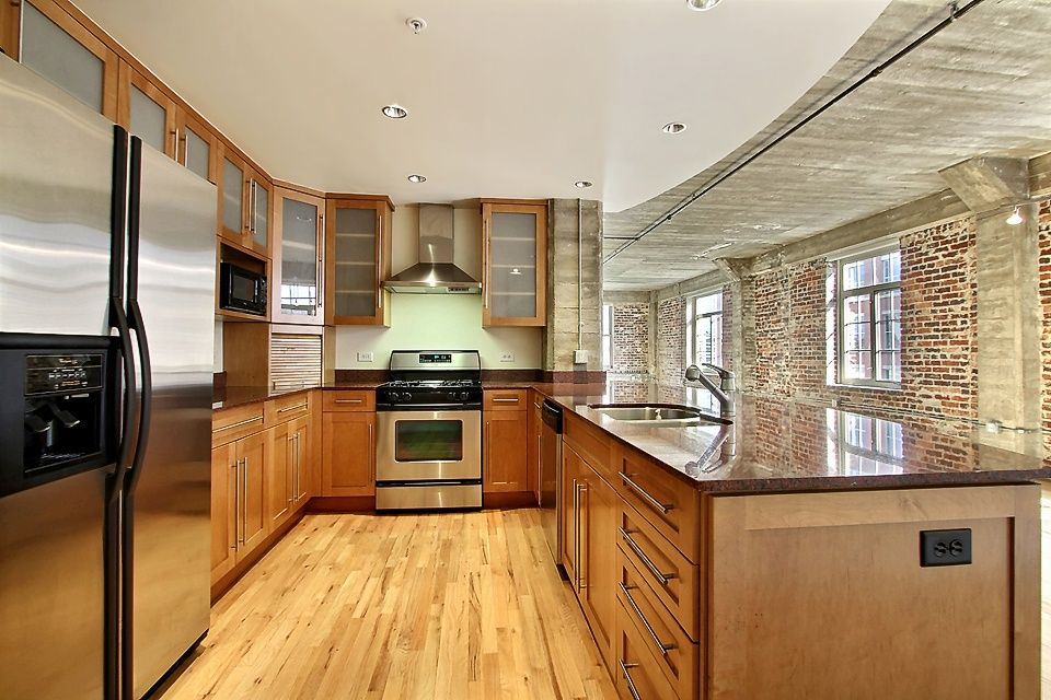 Contemporary Kitchen with dishwasher, Galley, Flat panel cabinets, Bamboo floors, Framed Partial Panel, Brick wall, Quartz