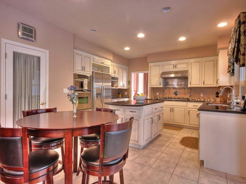 Traditional Kitchen with electric cooktop, can lights, Built In Refrigerator, double wall oven, stone tile floors, U-shaped