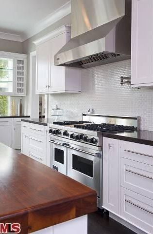 Contemporary Kitchen with Laminate floors, Soapstone counters, Glass panel, L-shaped, European Cabinets, Flush, Wood counters
