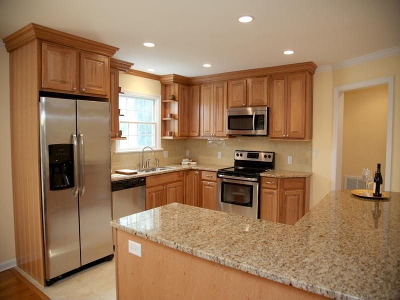Traditional Kitchen with can lights, Quartz countertop in giallo nova, Crown molding, Kitchen island, Concrete floors