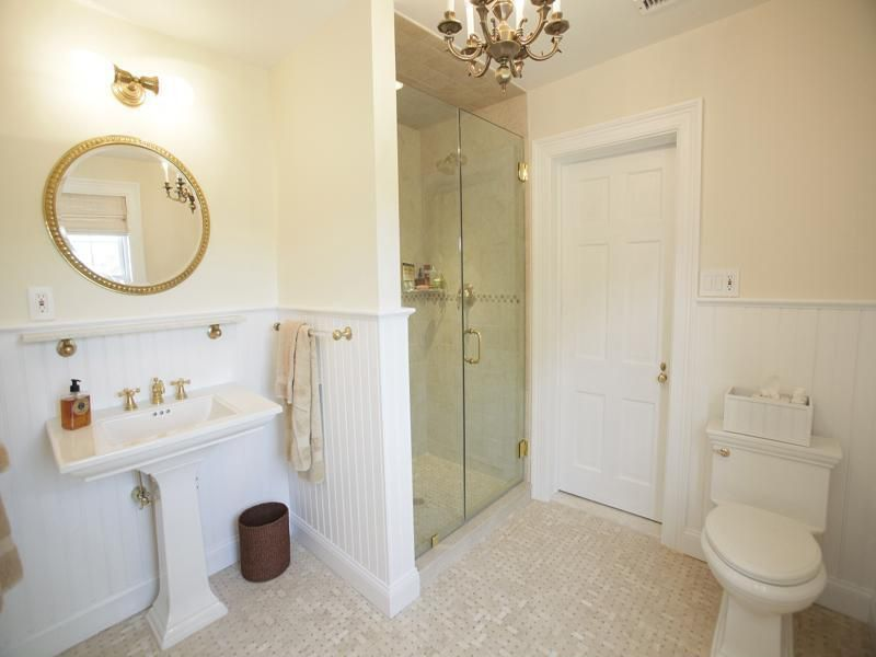 Traditional 3/4 Bathroom with Jamie young company ball chain mirror, specialty tile floors, Chandelier, Pedestal sink, Shower