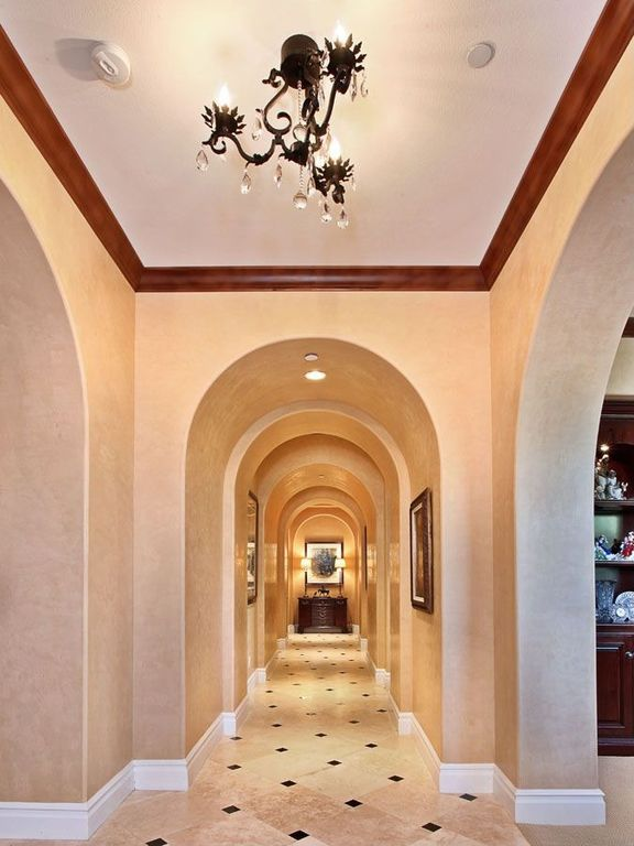 Mediterranean Hallway with travertine floors, Chandelier, can lights, High ceiling, Crown molding