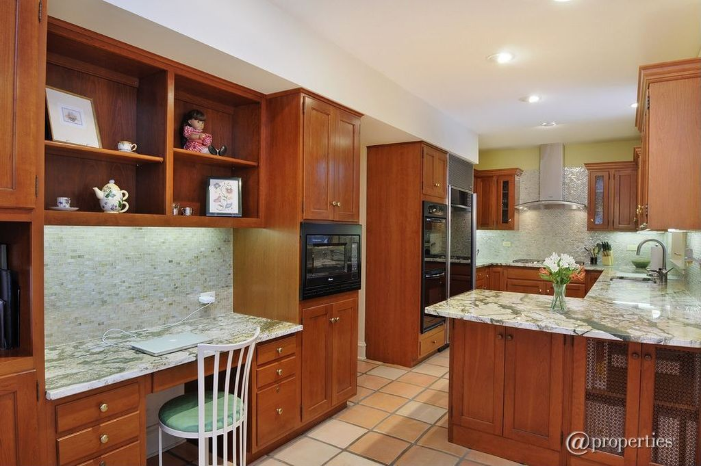 Traditional Kitchen with can lights, built-in microwave, Flat panel cabinets, Glass panel, Complex granite counters, Flush