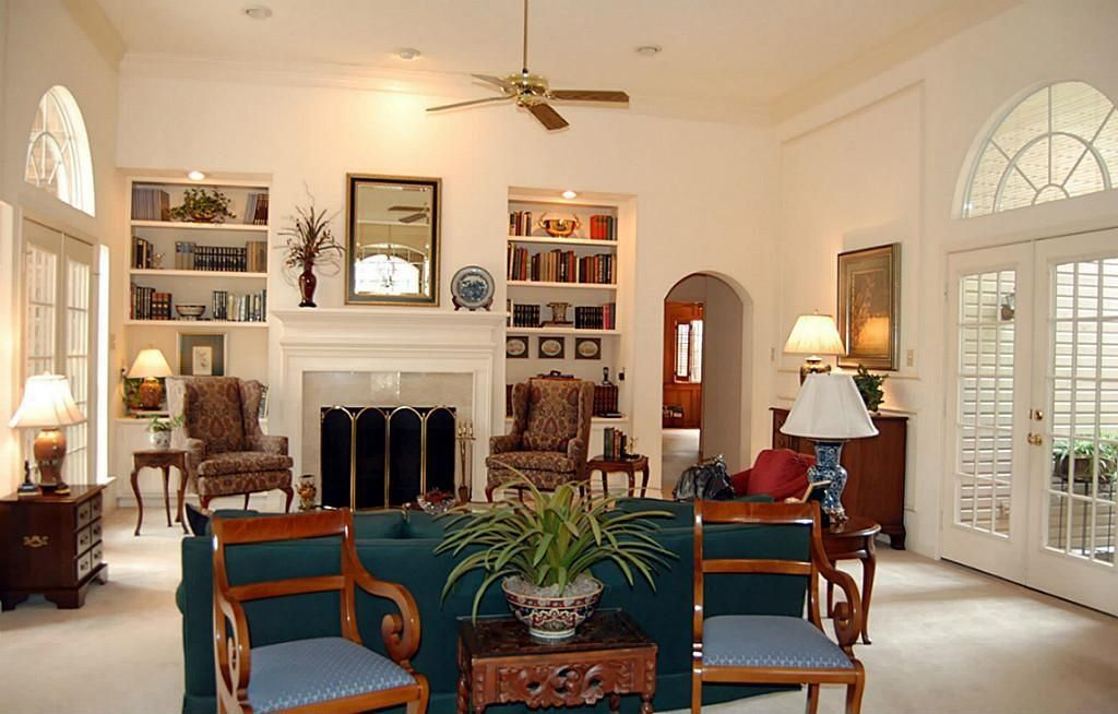 Traditional Living Room with Arched window, French doors, can lights, Fireplace, Carpet, Ceiling fan, Built-in bookshelf