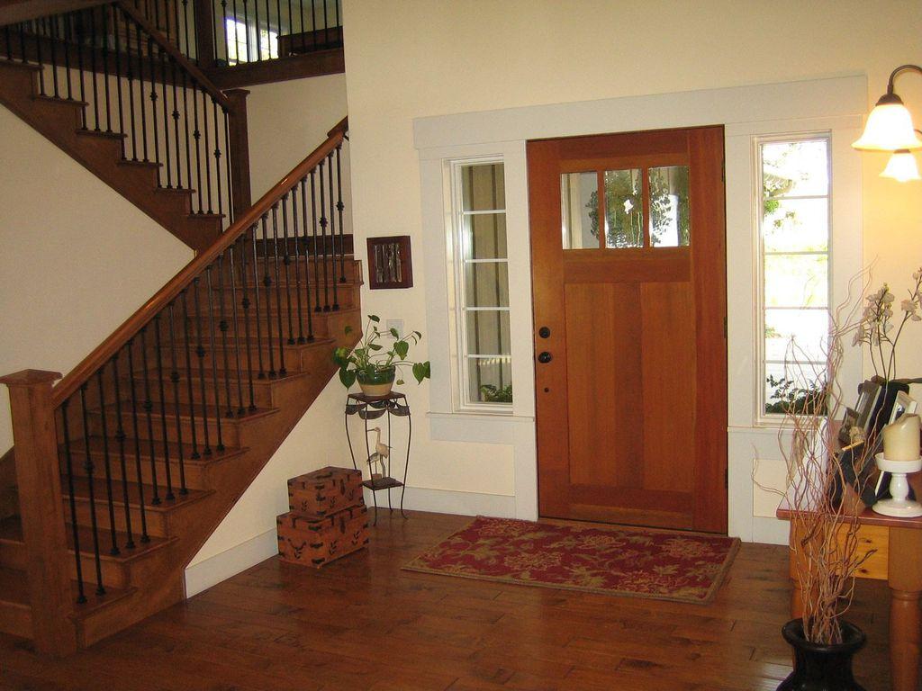 Craftsman Entryway with specialty window, Built-in bookshelf, Wall sconce, Glass panel door, Hardwood floors, Standard height
