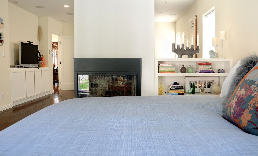 Contemporary Master Bedroom with flat door, Laminate floors, Fireplace, picture window, can lights, Standard height