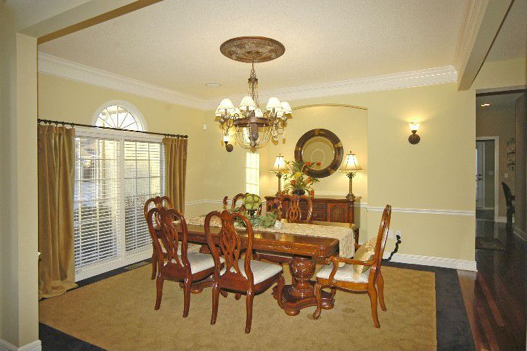 Traditional Dining Room with Crown molding, Wall sconce, Chandelier, Standard height, Chair rail, Arched window