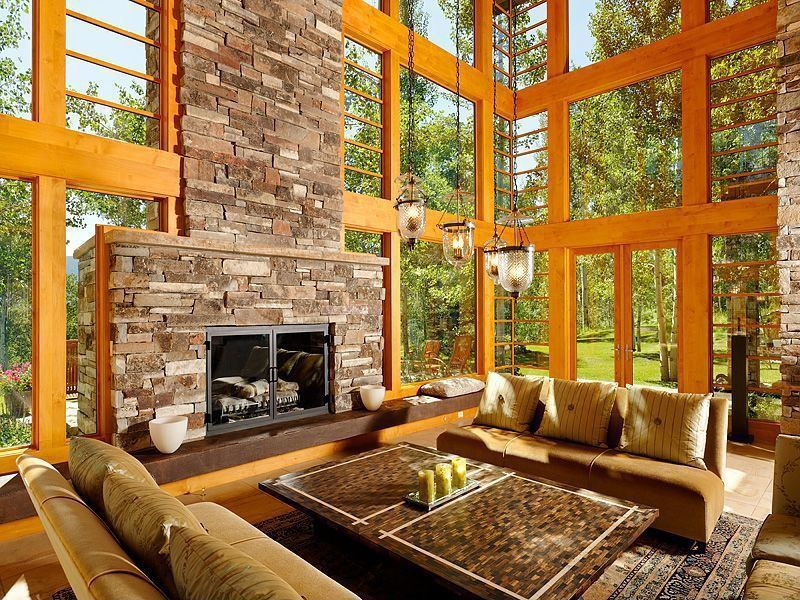 Mediterranean Living Room with Natural light, Stacked stone fireplace, Multi-level windows, High ceiling, French doors