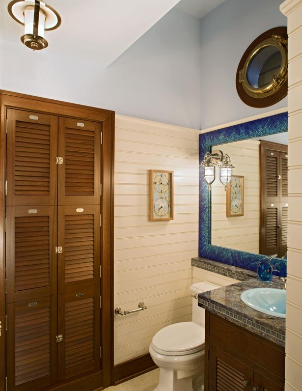 Cottage Powder Room with wall-mounted above mirror bathroom light, European Cabinets, drop-in sink, Inset cabinets