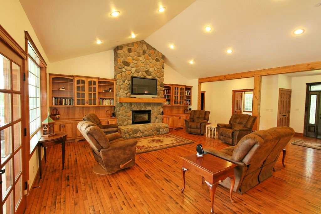 Country Living Room with Built-in bookshelf, River Rock - Faux Stone Panels - Winter Blend, Hardwood floors, French doors