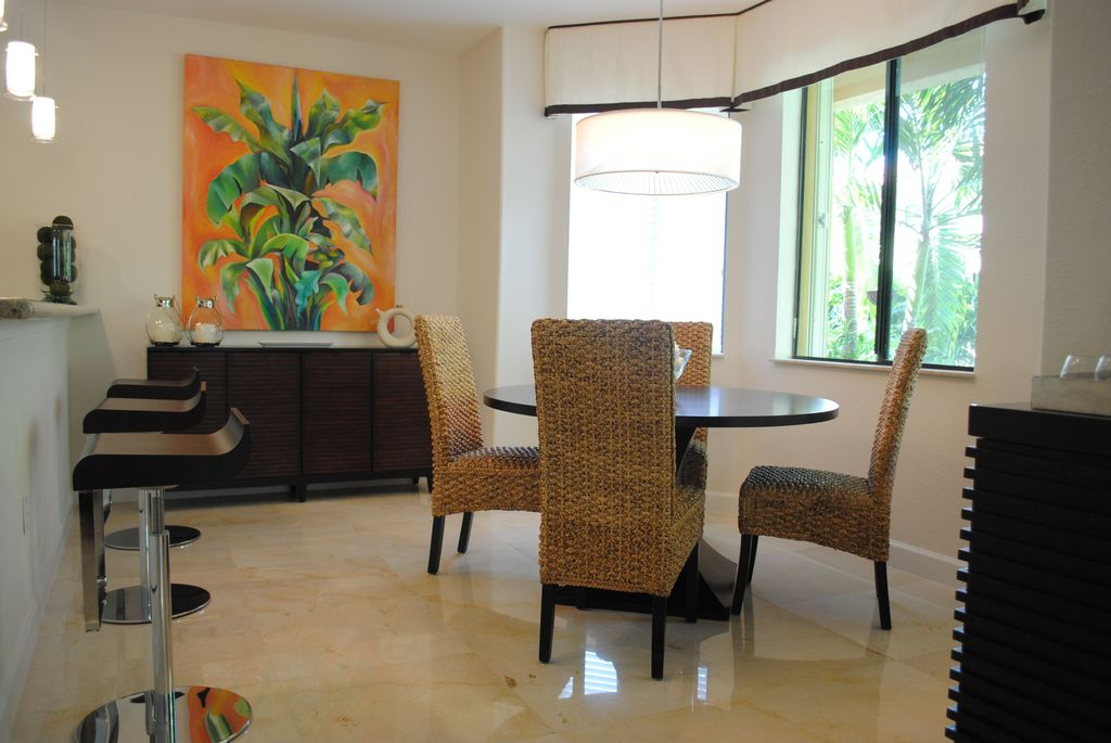 Tropical Dining Room with specialty window, flush light, stone tile floors, simple marble tile floors, Built-in bookshelf