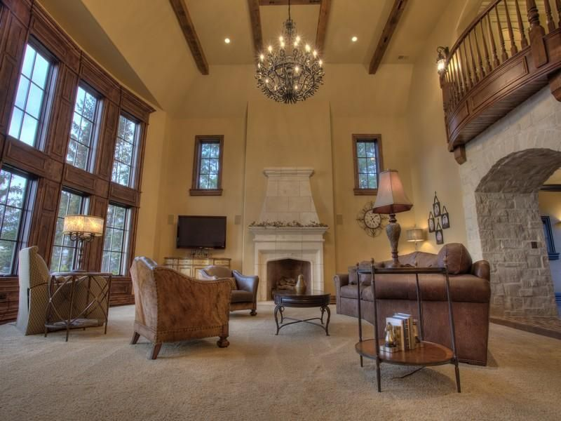Traditional Living Room with Cement fireplace, Carpet, Wall sconce, Exposed beam, Fireplace, Chandelier, Casement, can lights