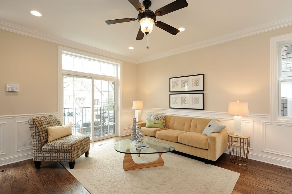 Traditional Living Room with Ceiling fan, Standard height, can lights, Wainscotting, Hardwood floors, Transom window