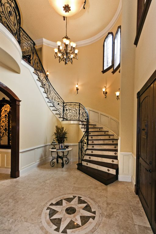 Traditional Staircase with Wall sconce, Cathedral ceiling, Arched window, flush light, Wainscotting, Chandelier, Barn door