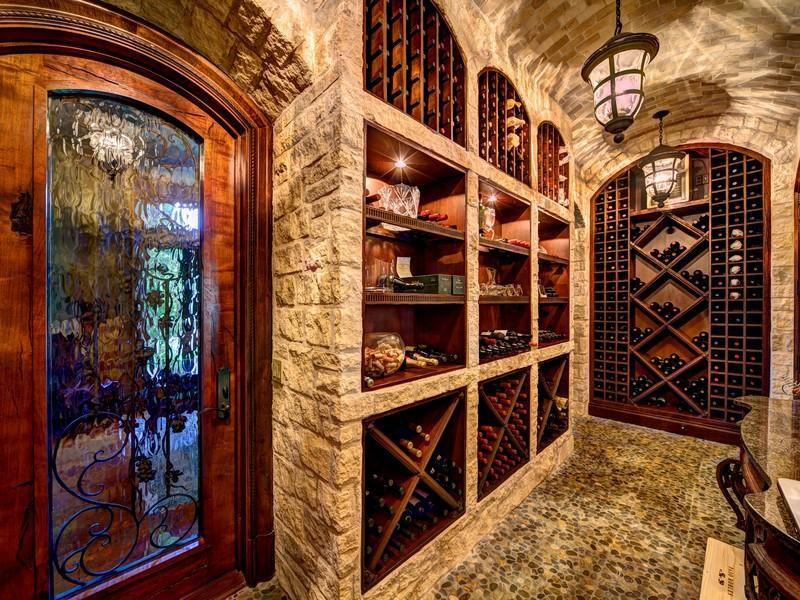 Mediterranean Wine Cellar with sandstone floors, Standard height, can lights, Pendant light, specialty door