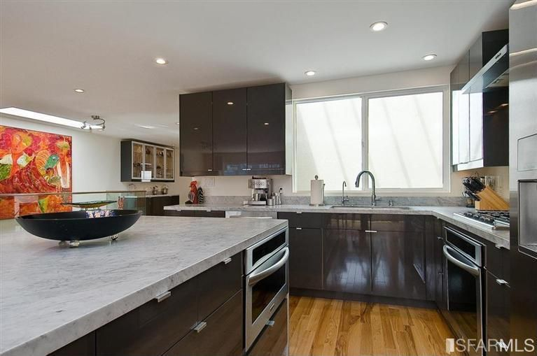 Contemporary Kitchen with partial backsplash, Casement, wall oven, electric cooktop, Undermount sink, Complex marble counters