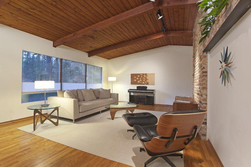 Contemporary Living Room with picture window, Exposed beam, Hardwood floors, flush light, Standard height, interior brick