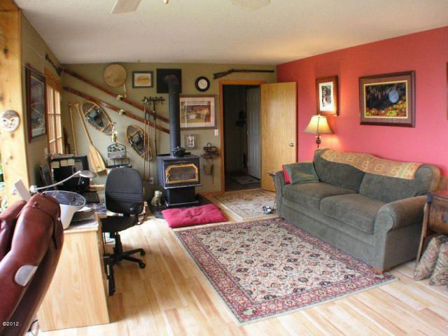 Craftsman Living Room with flat door, Standard height, Wood Stove fireplace, Hardwood floors, Fireplace, Ceiling fan