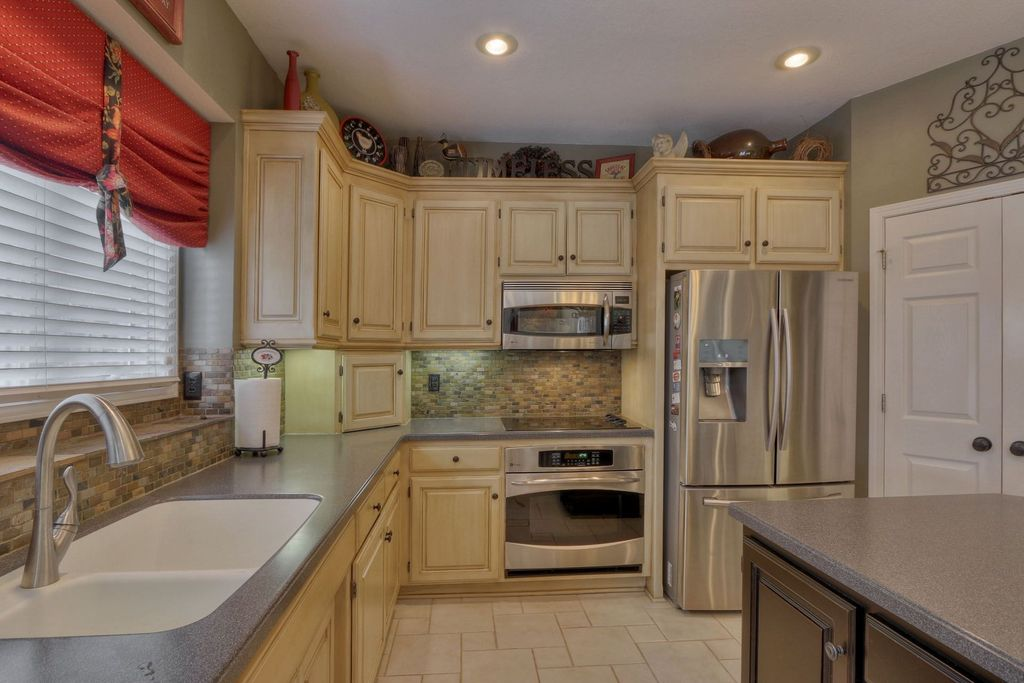 Traditional Kitchen with limestone tile floors, Multiple Sinks, Multiple Refrigerators, Simple granite counters, L-shaped