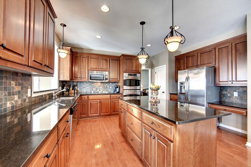 Traditional Kitchen with Pendant light, Inset cabinets, specialty door, Undermount sink, Simple granite counters, U-shaped