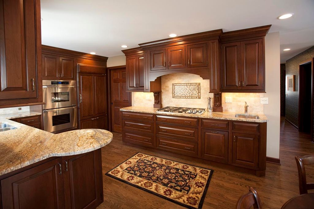 Traditional Kitchen with Framed Partial Panel, Limestone Tile, Multiple Sinks, electric cooktop, Undermount sink, Custom hood