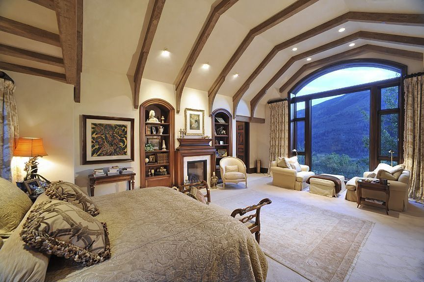 Craftsman Master Bedroom with can lights, Carpet, picture window, Fireplace, Built-in bookshelf, High ceiling, Exposed beam