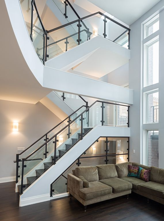 Modern Staircase with Wall sconce, Casement, Glass staircase, High ceiling, Hardwood floors