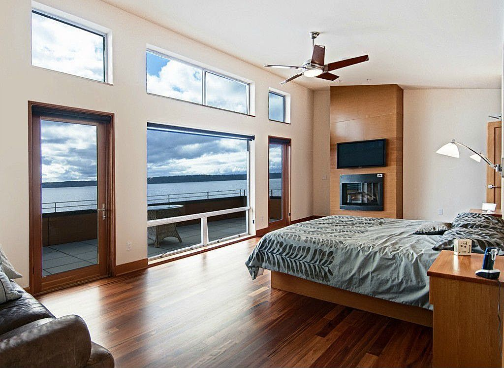 Contemporary Master Bedroom with Fireplace, specialty window, French doors, can lights, Hardwood floors, Built-in bookshelf