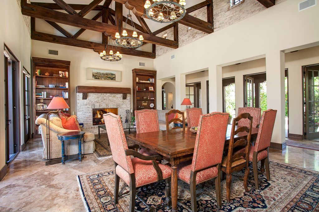 Traditional Dining Room with travertine tile floors, Columns, interior brick, Chandelier, Exposed beam, picture window