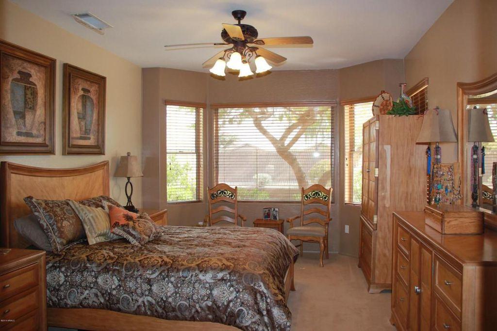 Mediterranean Master Bedroom with double-hung window, Ceiling fan, Built-in bookshelf, picture window, Carpet