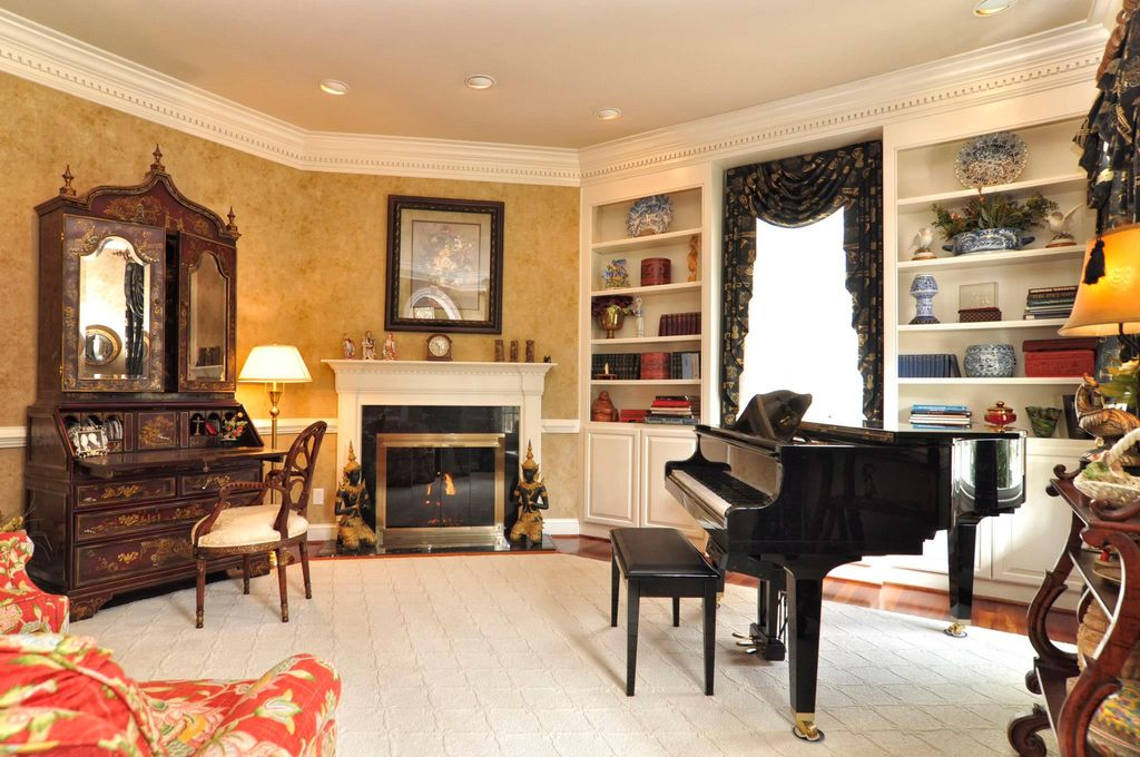 Traditional Living Room with Standard height, stone fireplace, Chair rail, Built-in bookshelf, can lights, interior wallpaper