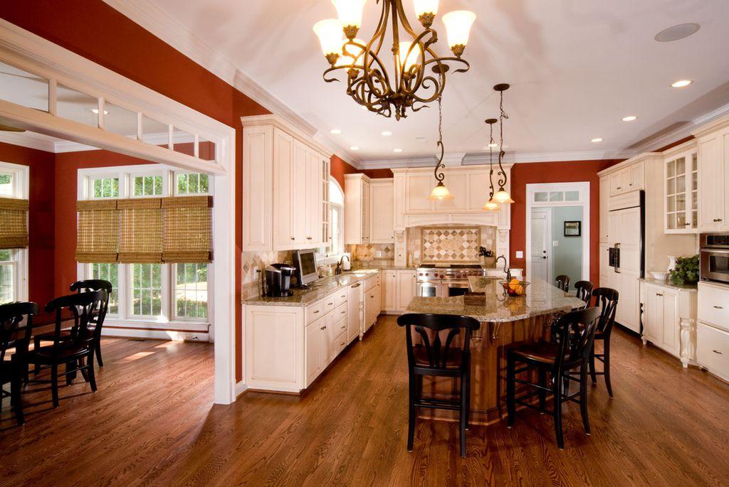 Mediterranean Kitchen with Pendant light, Custom hood, Limestone Tile, Undermount sink, Simple granite counters, Stone Tile
