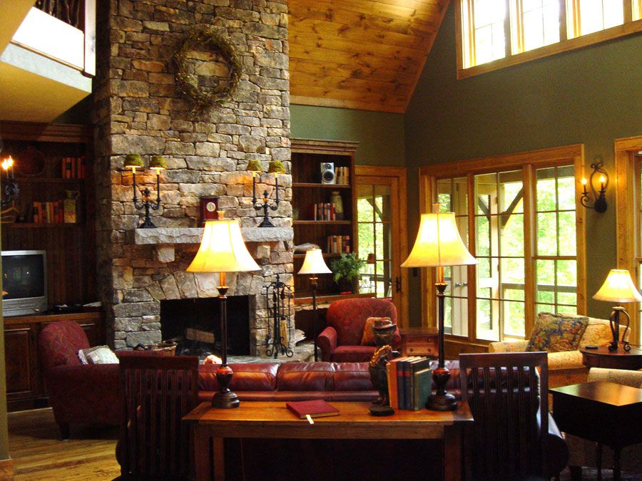Rustic Living Room with Wall sconce, Built-in bookshelf, High ceiling, Fireplace, stone fireplace, Hardwood floors