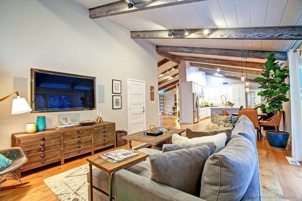 Rustic Living Room with Exposed beam, specialty door, Standard height, Hardwood floors, flush light