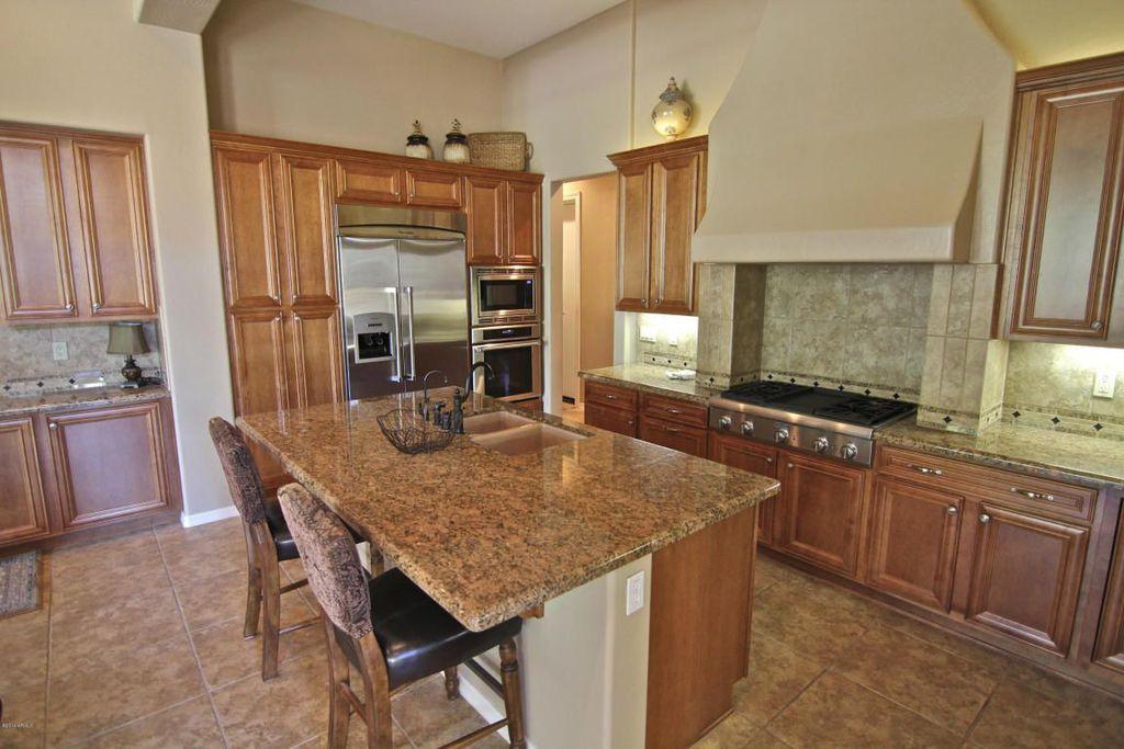 Traditional Kitchen with Complex granite counters, Mitered cabinet doors in dark walnut stain, Breakfast bar, Wire basket