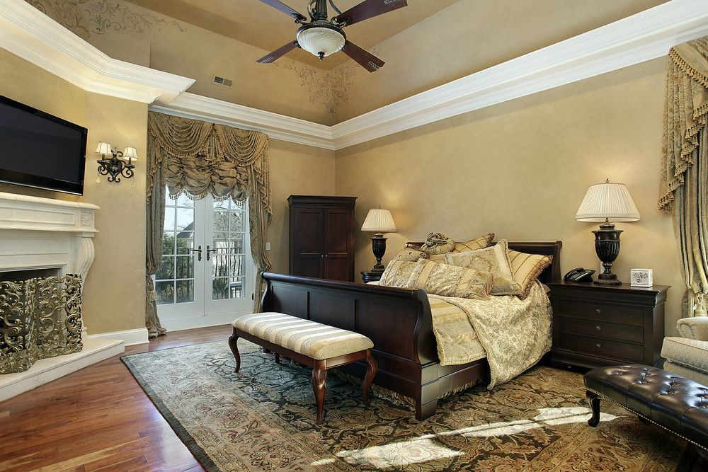 Traditional Master Bedroom with Wall sconce, Hardwood floors, Ceiling fan, French doors, stone fireplace, High ceiling