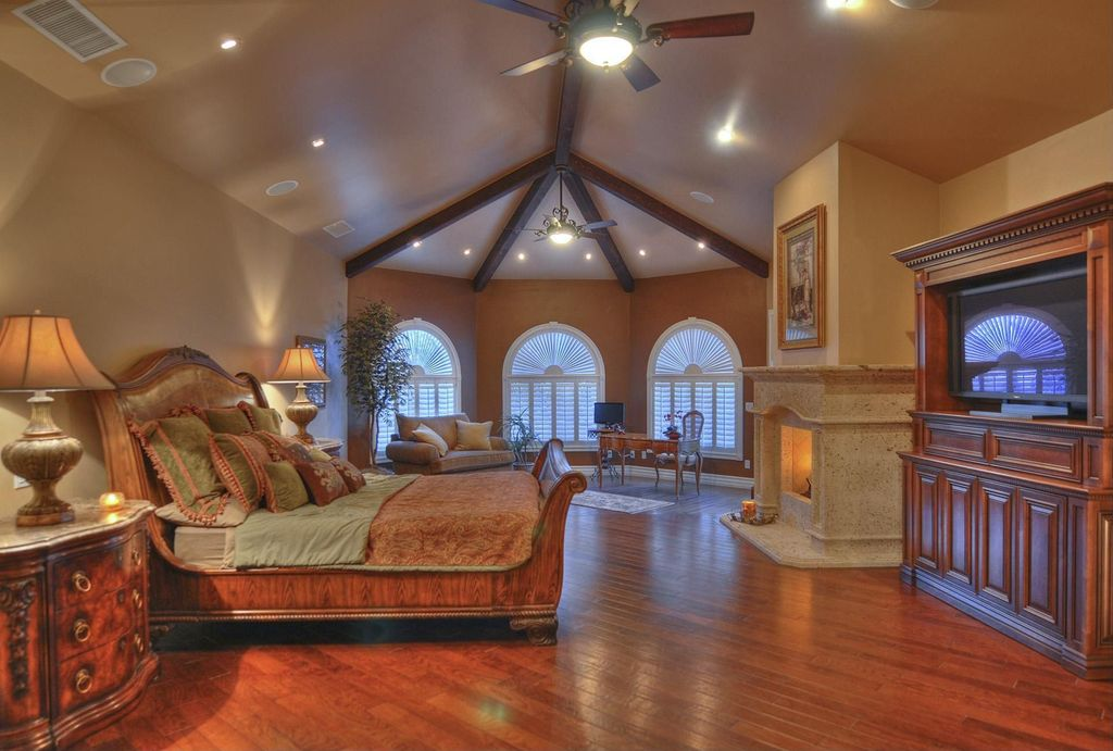 Mediterranean Guest Bedroom with High ceiling, Cement fireplace, Exposed beam, Fireplace, Ceiling fan, Hardwood floors