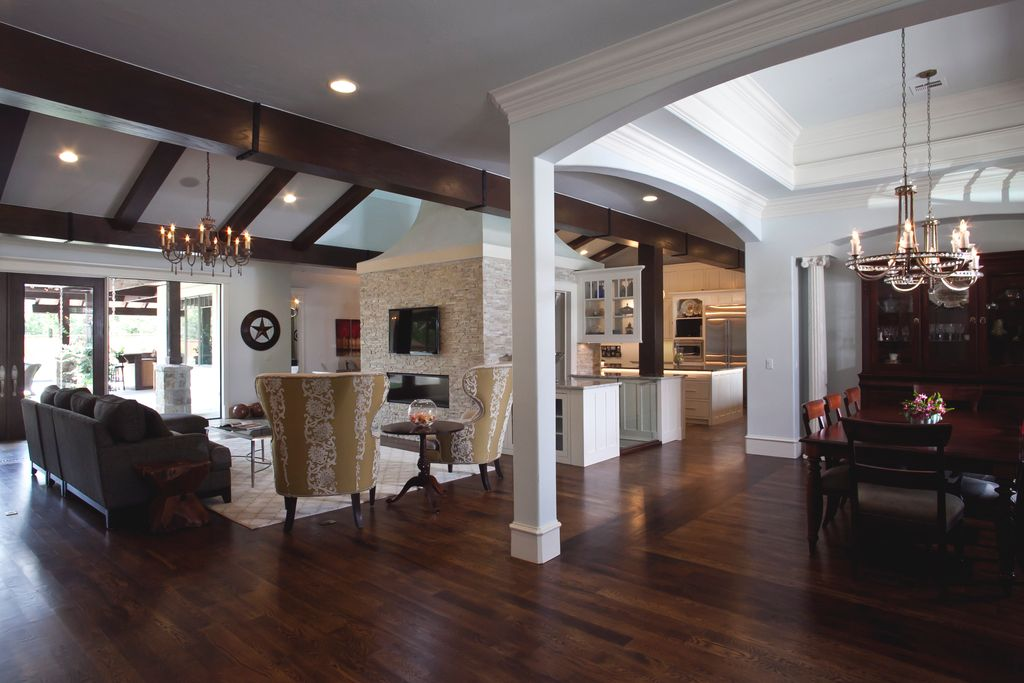 Traditional Great Room with Exposed beam, Fireplace, Crown molding, Columns, High ceiling, Built-in bookshelf, Chandelier