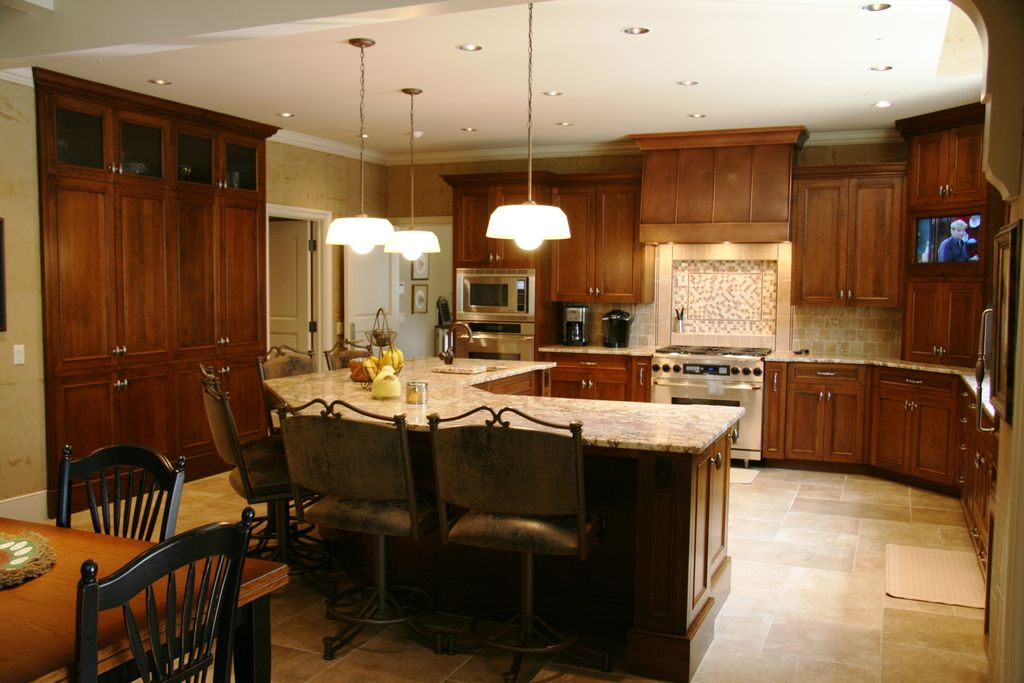 Traditional Kitchen with Complex granite counters, Breakfast nook, Pendant light, Breakfast bar, stone tile floors, gas range