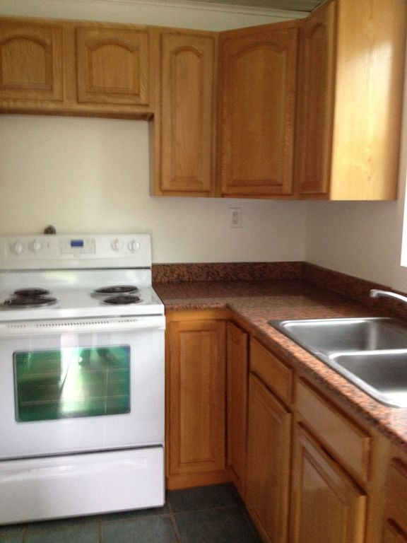 Traditional Kitchen with Simple Granite, stone tile floors, L-shaped, gas range, partial backsplash, Crown molding