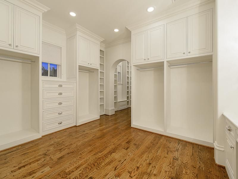 Traditional Closet with Crown molding, Hardwood floors, California Closets Custom Wardrobe, Built-in bookshelf