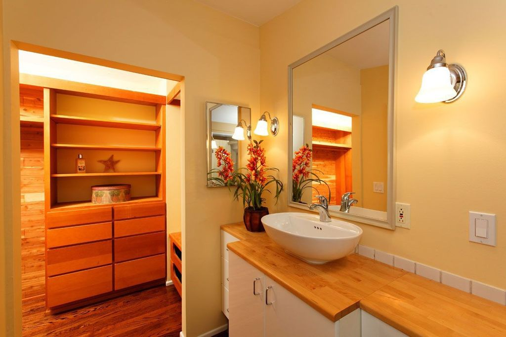 Modern Powder Room with Built-in bookshelf, Wall sconce, Wood counters, Framed Partial Panel, Standard height, Vessel sink
