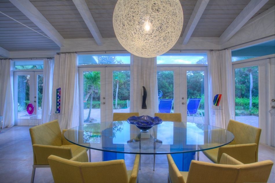 Contemporary Dining Room with Standard height, Pendant light, Exposed beam, specialty window, French doors, Concrete tile