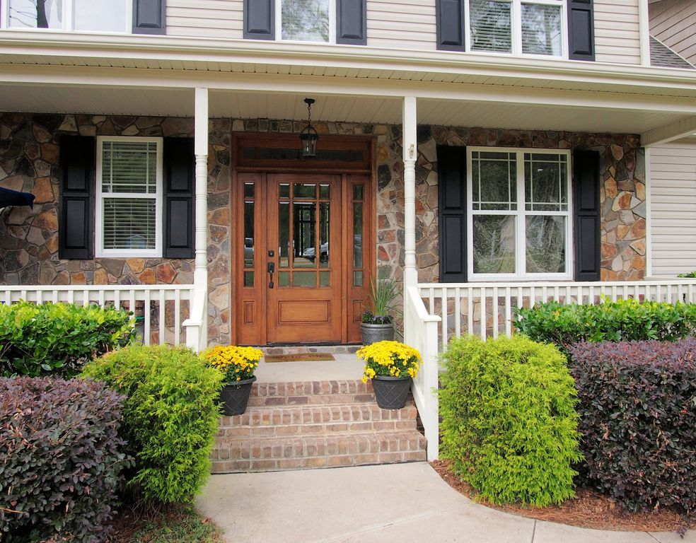 Traditional Front Door with exterior concrete tile floors, Glass panel door, double-hung window, Deck Railing, Pathway
