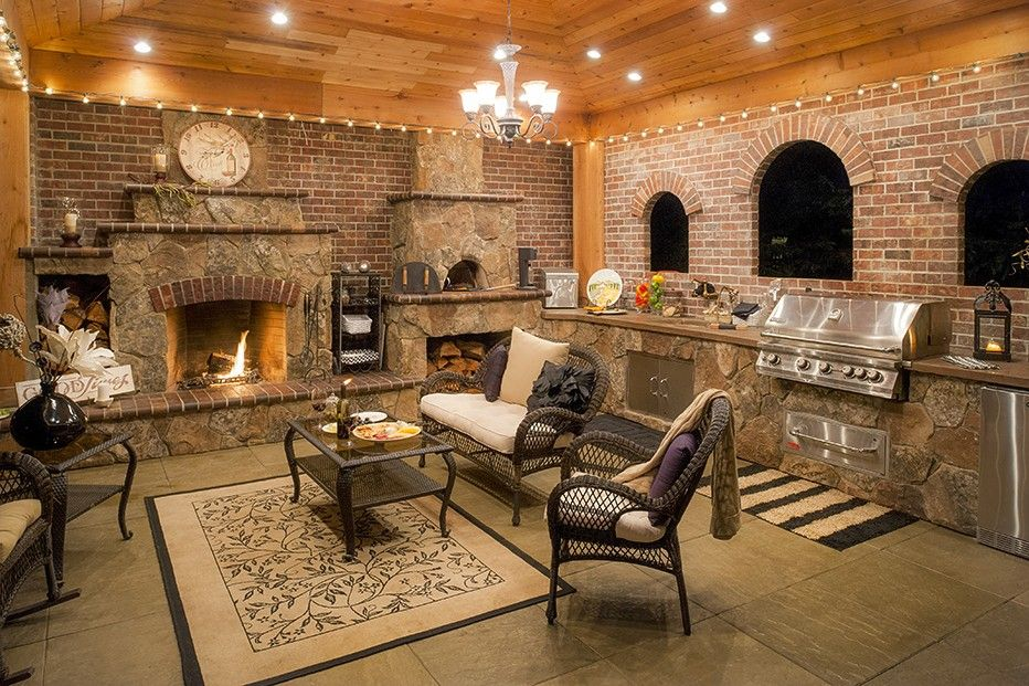 Rustic Porch with exterior stone floors, Wrap around porch, outdoor pizza oven, Outdoor kitchen