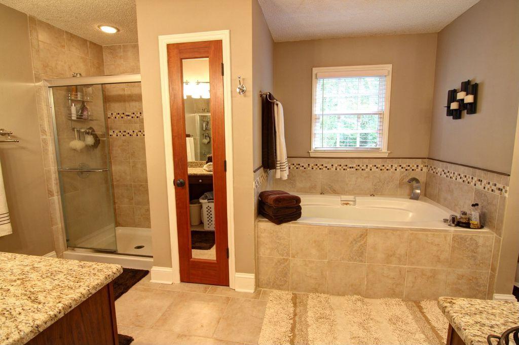 Craftsman Master Bathroom with Wall Tiles, flush light, framed showerdoor, Complex granite counters, Casement, Bathtub