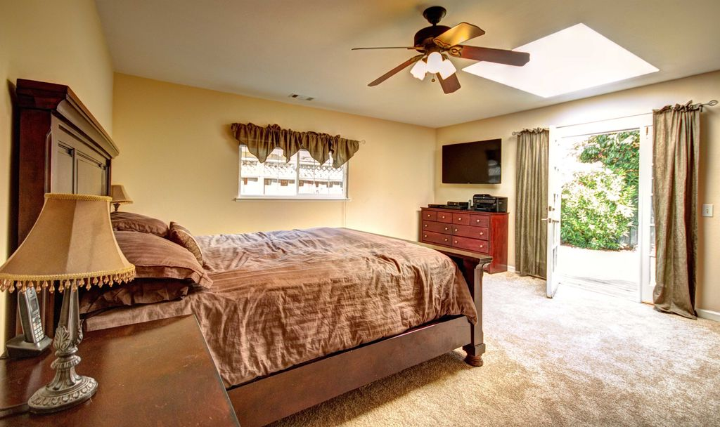 Traditional Master Bedroom with picture window, Ceiling fan, French doors, Carpet, Paint, Standard height, flush light