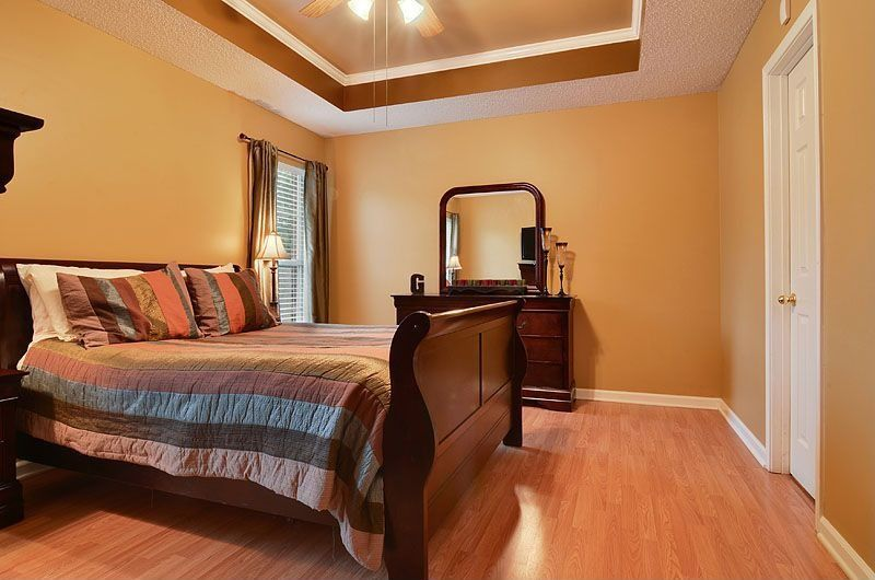 Traditional Master Bedroom with double-hung window, Ceiling fan, Laminate floors, six panel door, Standard height