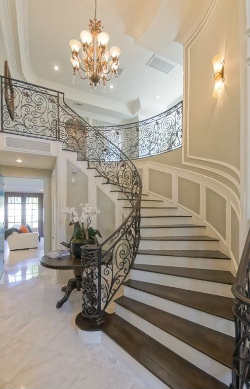 Traditional Staircase with Crown molding, Wall sconce, Hardwood floors, Wainscotting, High ceiling, Chandelier