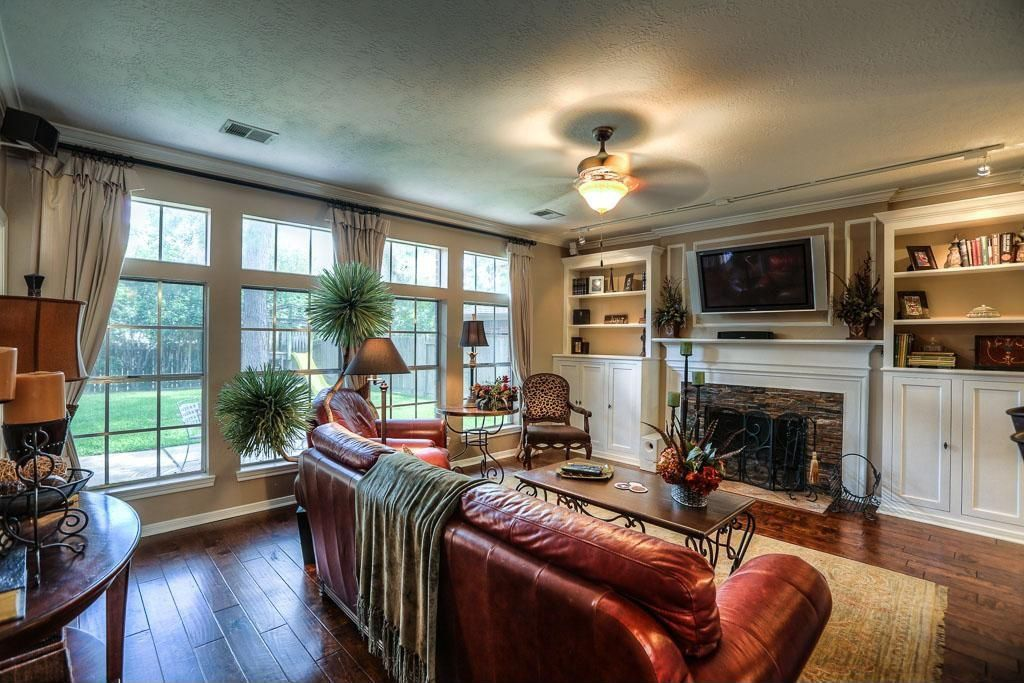 Traditional Living Room with flush light, Ceiling fan, double-hung window, Fireplace, picture window, Hardwood floors